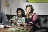 Friends playing video games wearing gaming headphones