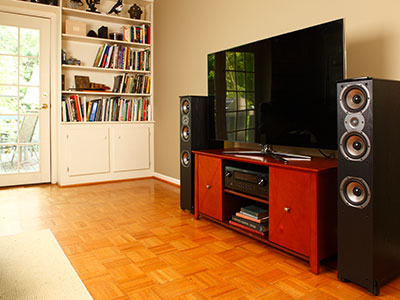 Floor-standing speakers beside the TV