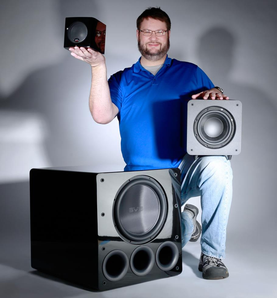 Author Josh Crane with three subwoofers of varying sizes. SVS PB13-Ultra, Polk Audio PSW111, PSB SubSeries 100