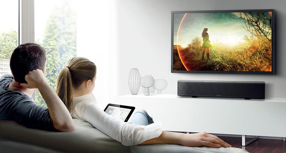 photo of a couple watching TV, listening to a Yamaha YSP-5600 Digital Sound Projector
