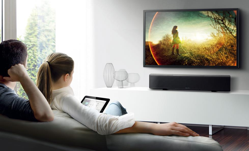 Place a sound bar on a stand below a wall-mounted TV