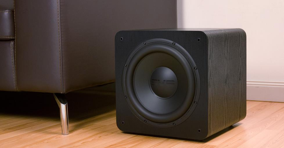 A powered subwoofer sitting on the floor next to a couch.