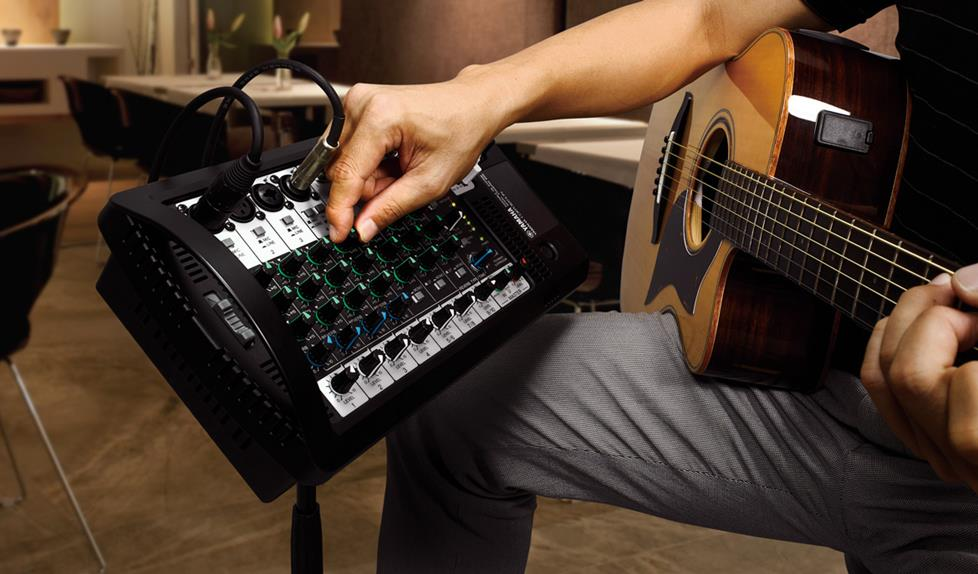 Guitar player adjusting portable PA mixer