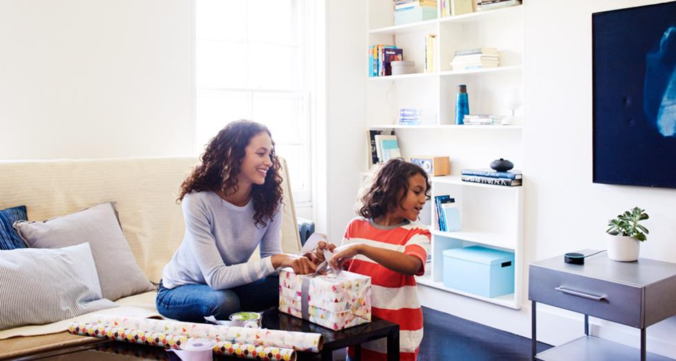 Mother and daughter wrapping gifts, interacting with voice assistant