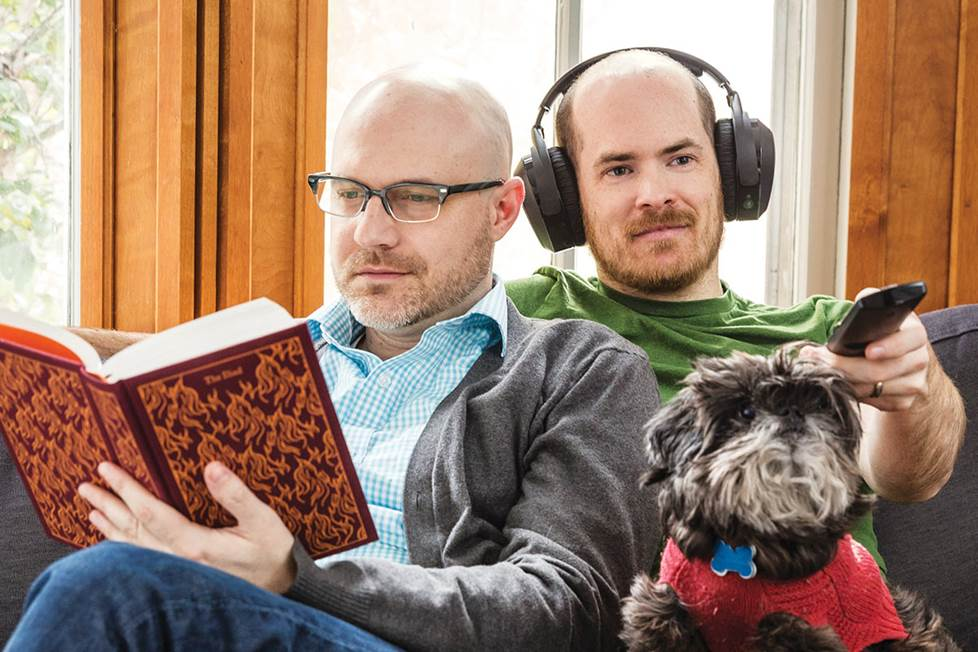 couple on couch with dog reading and listening to TV with headphones