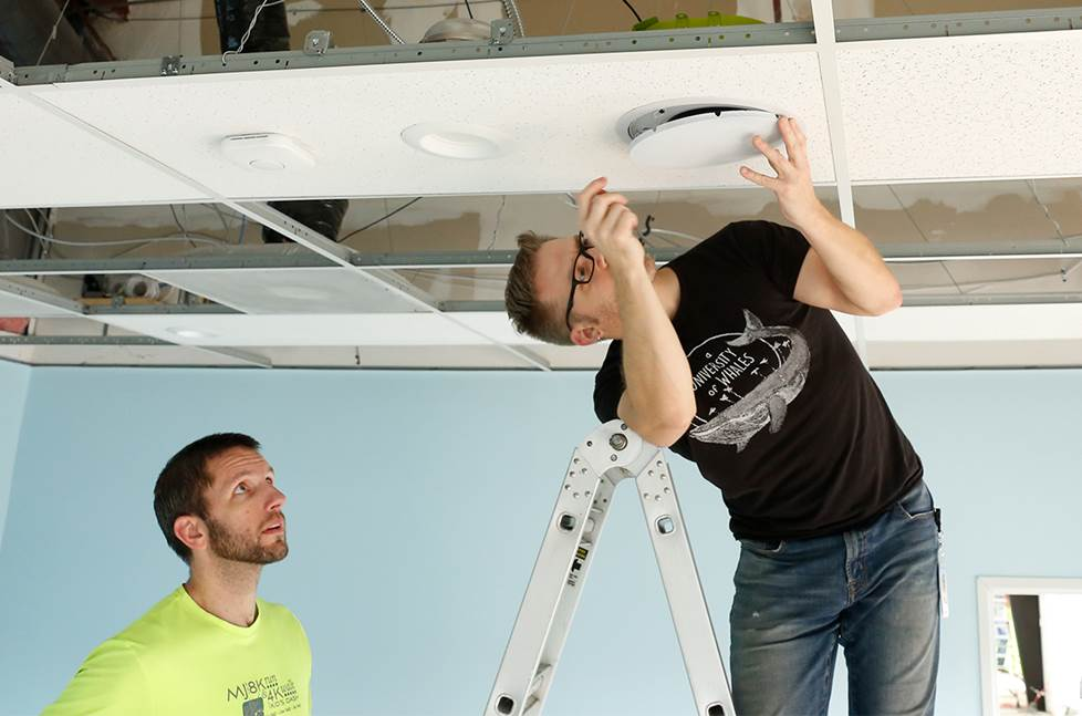 two guys working on an in-ceiling speaker