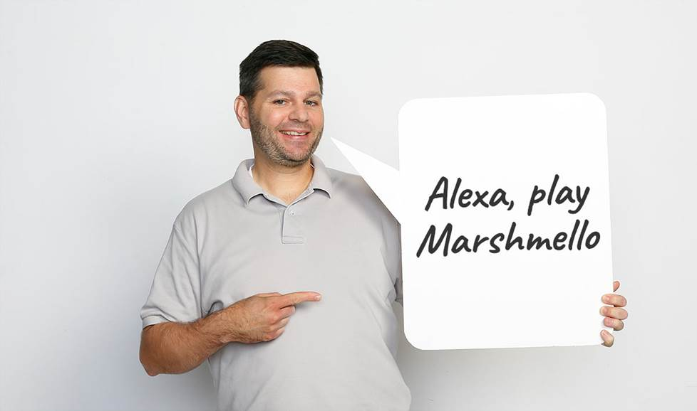 "Man holding speech bubble saying ""Alexa, play Marshmello"""