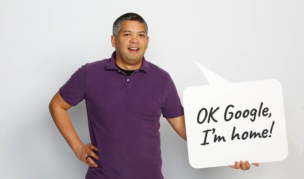 "Man holding speech bubble that says ""OK Google, I'm home"""