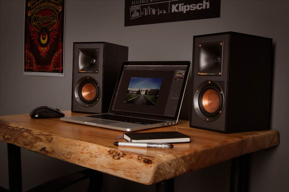 Klipsch desktop speakers sitting on a desk next to a computer.
