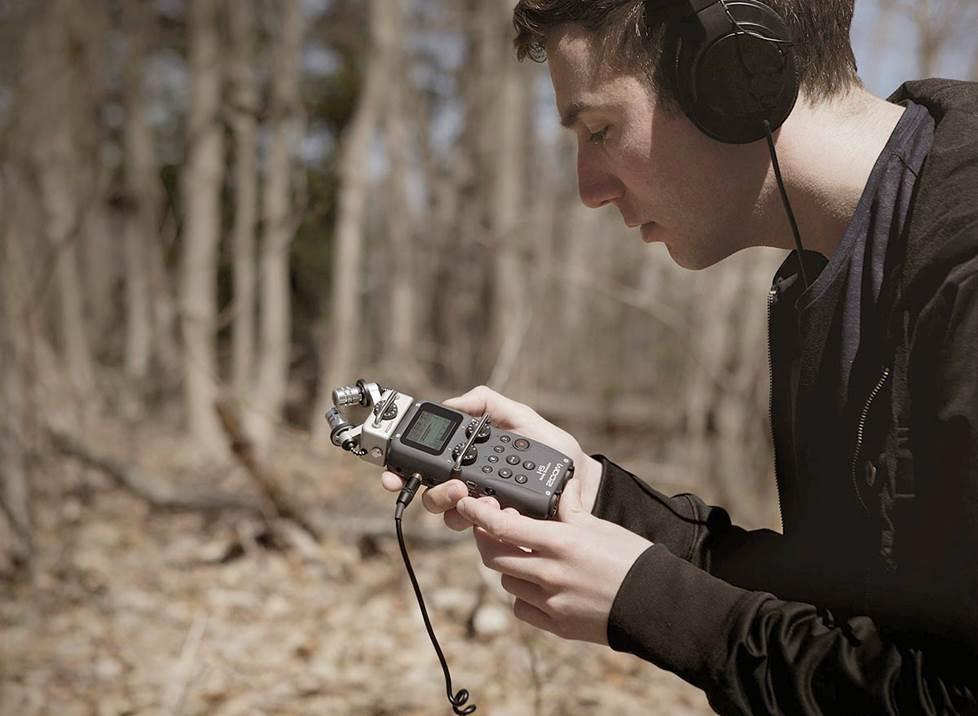 Man outside making field recordings