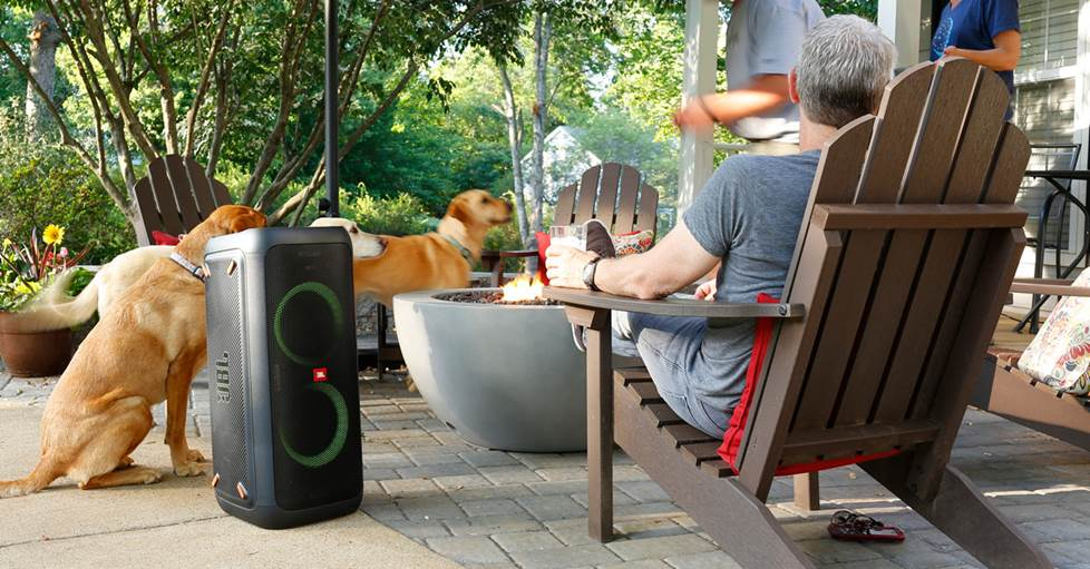 JBL PartyBox 300 Portable Bluetooth® speaker with light display in use near a fire pit.
