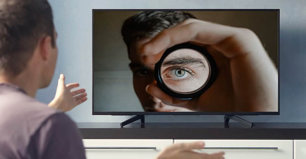 A man watching at TV. On the TV is a man looking back at the viewer.