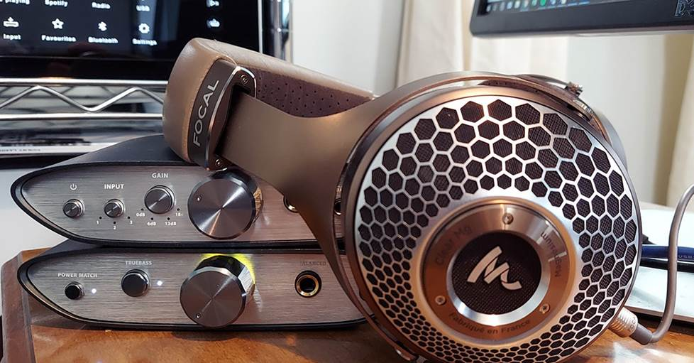 Image of Focal Clear MG beside two amps.