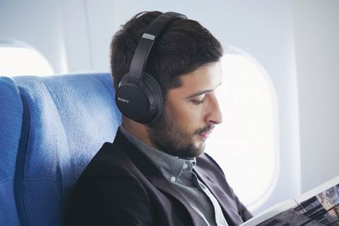 Man wearing Sony WH-CH700N headphones on plane
