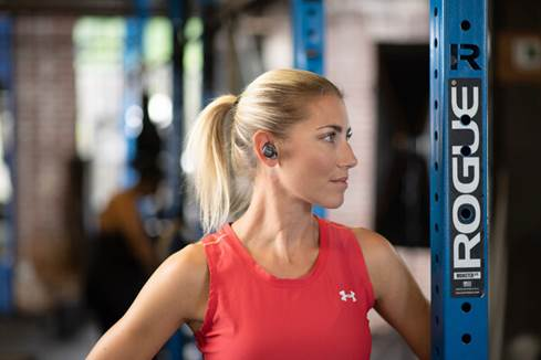 Woman working out wearing Cleer Ally earbuds