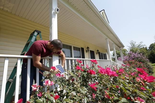 Advisor Carlos installs Ring Spotlight Cam Battery and Solar Panel bundle on his front porch.