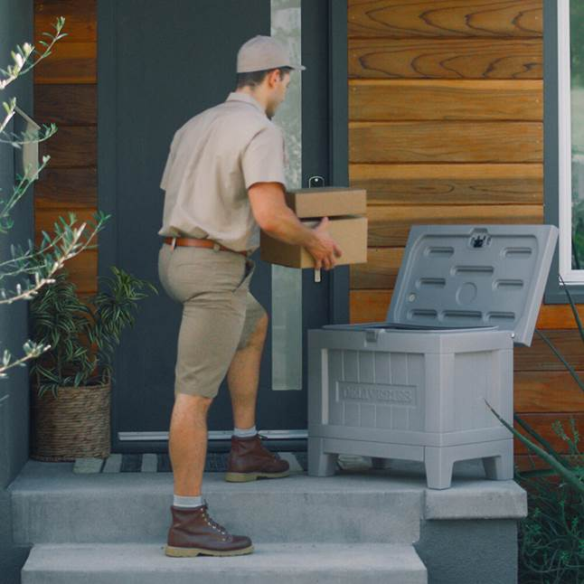 UPS guy putting packages in Yale Kent Smart Delivery Box on porch