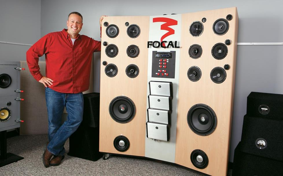 Jordan posing in front of the Focal speaker board